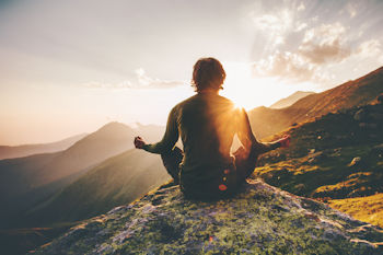 Inspirational health articles - person healthy meditating on mountain