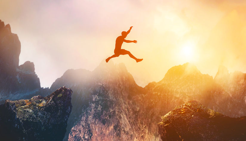 Man jumping between rocks to represent overcoming a problem