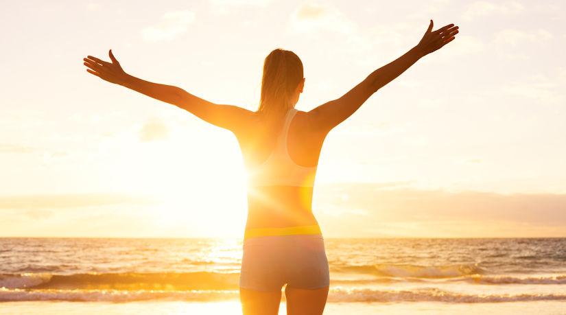 Woman at sunset facing the ocean with hands up in success