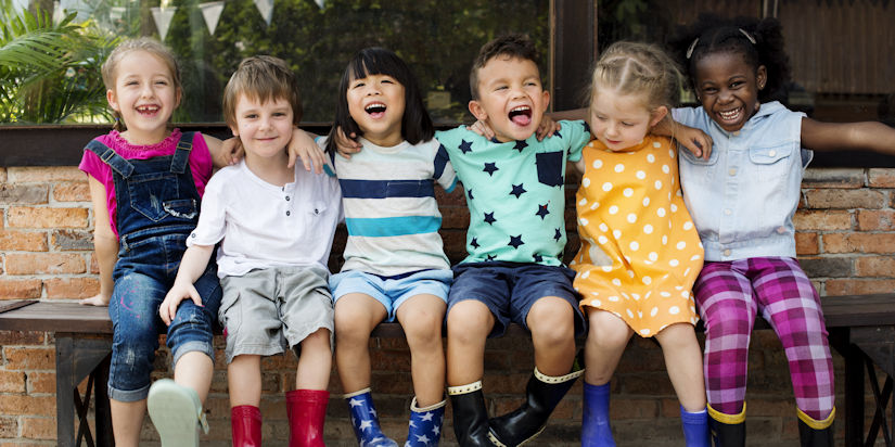Group of kindergarten friends with their arms around each other while sitting and smiling