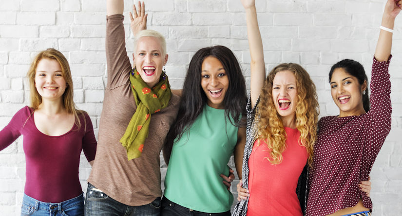 Group of happy women with their arms up smiling